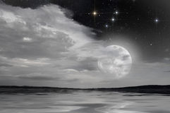 Full moon over the lake. The light dela full moon in a starry sky reflected on the calm waters of a lake stock photos