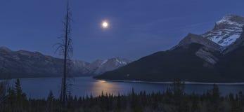 Full Moon over Lake Minnewanka in Banff National Park. Night Landscape View of Full Moon over Lake Minnewanka in Banff National Park, Rocky Mountains Alberta Stock Image