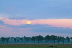 Full moon over meadows at sunrise Stock Image