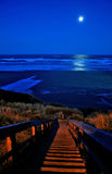 Full moon over Newport beach. Scenic view of full moon over blue sea at night with illuminated steps in foreground, Newport, Oregon, U.S.A Stock Photo
