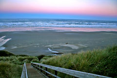 Full moon over Newport Beach. Sunrise with a full moon over Newport Beach Oregon with a tall sea grass in the foreground Stock Photography
