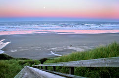 Full moon over Newport Beach. Sunrise with a full moon over Newport Beach Oregon with a tall sea grass in the foreground Royalty Free Stock Photos