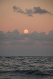 Full moon over ocean and clouds Stock Image