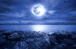 Full moon over the ocean. With clouds and rocks Stock Photography