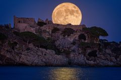 Full moon over the old castle in Costa Brava in a holiday village Fosca , Spain stock photo