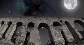 Full moon over the Roman aqueduct. View of a Roman aqueduct under the full moon and the starry sky royalty free stock image