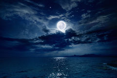 Full moon over sea. Night sky with full moon and reflection in sea, stars, beautiful clouds. Elements of this image furnished by NASA Stock Image