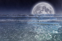 Full moon over sea. Full moon rising from the ocean at night Royalty Free Stock Photo