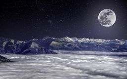 The full moon over snowy Alps, above clouds, under the starry sky Stock Photos