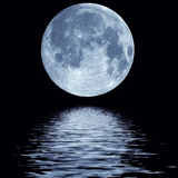 Full moon over water. Full blue moon over cold night water Stock Image