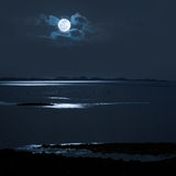 Full Moon over water. Full Moon over calm sea with a distanc shore Stock Image