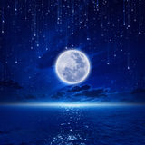 Full moon. Peaceful background, night sky with full moon and reflection in sea, falling stars, glowing horizon. Elements of this image furnished by NASA Royalty Free Stock Photo