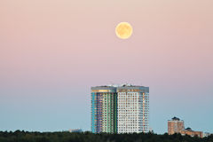 Full moon in pink sky over urban houses Stock Photo