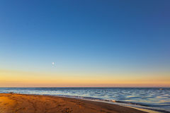 Full moon on a rainbow sky. A flock of seagulls at sunset on a winter day fly over the full moon, Catania, Italy Royalty Free Stock Photography