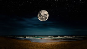Full moon reflected on the beach Stock Photo