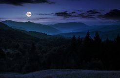 Full moon rise above forested mountain at night. Gorgeous Carpathian nature scenery Stock Images