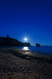 Full moon rise on a rocky beach Stock Images