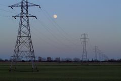 Full moon rising. Full moon rises at dusk over flat farmland and a line of (British) electricity pylons royalty free stock images