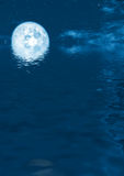 Full moon rising. From calm water Stock Image