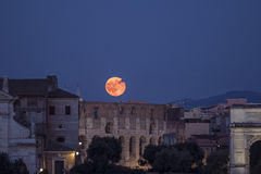 The Full Moon is rising above the Colosseum, Rome, celebrating the 47th anniversary from the Apollo 11 landing Stock Photos