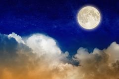 Full moon rising above glowing clouds in night sky. Elements of this image furnished by NASA Stock Photo