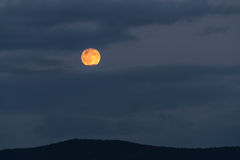 Full moon rising behind clouds royalty free stock photography