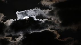Full moon rising from behind the dark clouds stock footage