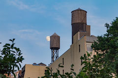 Full moon rising behind water tower on the roof of buildings in Royalty Free Stock Photo