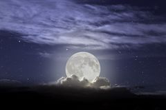 Full moon rising. In a cloudy night stock photography