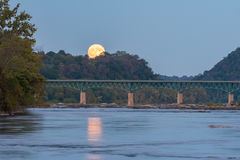 Full Moon Rising Over Bridge. The October full moon, sometimes called a Hunter`s Moon, rises above the Potomac River and a bridge connecting Maryland and stock photography