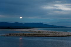 Full moon rising over lake & sea landscape at dusk. Full moon rising at dusk over mountains, lake, and sea. Location: Mallacoota, East Gippsland, Victoria stock image