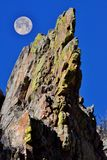 Full moon rising over the mountains. A bright full moon rise over a dramatic mountain cliffs Royalty Free Stock Image