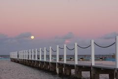 Full moon rising over the ocean at sunset Royalty Free Stock Images