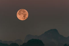 Full moon set in morning behind Mountain Stock Images