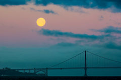 The full moon setting behind the Golden Gate Bridge and the fog just before sunrise. Stock Images