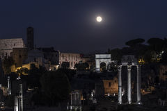 Full Moon shining above the Roman Forum and the Colosseum in Rome, Italy. A breathtaking view on the Roman Forum, with the Colosseum on the background, while a Stock Image