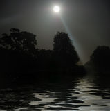 Full Moon Shining Above Water. Full Moon shining above tree silhouettes and water Stock Photo