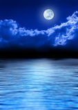 Full Moon Sky And Ocean. A full moon glowing in a night sky with a shimmering blue ocean below royalty free stock photos