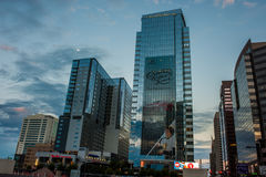 Full moon slightly obscured by clouds in desert sky. Downtown Phoenix business district reflecting the morning light on August 11, 2017.  Incoming storm clouds Stock Image