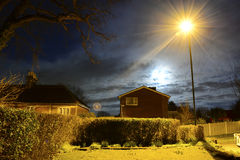 Full Moon and Street Light. An old oak tree looks dramatic at night during a full moon with an epic cloudscape and star bursting street light Stock Photography