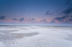 Full moon and sunrise sky over sand beach Royalty Free Stock Photo