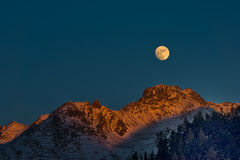 Full moon at sunset on winter mountains. Colored in Switzerland Royalty Free Stock Image