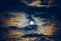 Full moon or supermoon in night blue sky with clouds, dramatic mysterious atmosphere royalty free stock image