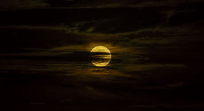 Full moon surrounded by silky clouds at night Royalty Free Stock Photography