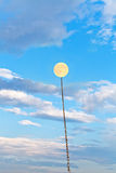 Full moon tied on chain soars into blue sky Royalty Free Stock Photo