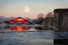 Full moon on top of rowing club in winter morning. Full moon up on the rowing club and ice on Corrib river in cold winter morning Royalty Free Stock Photo