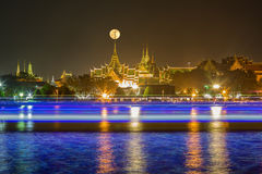 Full moon on top of wat Phra kaew. With light trails from boats in Chao phraya river stock photo