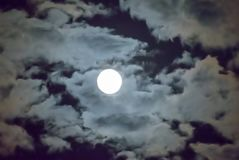 Beautiful full moon and white cloudy sky background in the midnight sky background, moonlight on Halloween night without stars. Full moon and white cloud sky in Stock Image