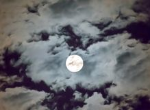Beautiful full moon and white cloudy sky background in the midnight sky background, moonlight on Halloween night without stars. Full moon and white cloud sky in stock photos