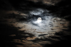 Full moon and white clouds on black night sky Stock Photo